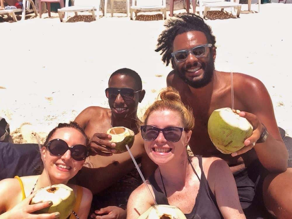Jame and Sarah with friends drinking coconut