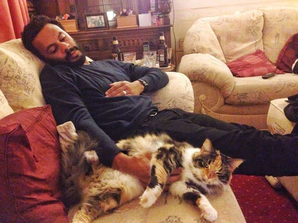 Chilling out with their cat after a belly full of cheese