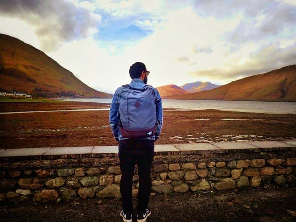 James with backpack with mountain view