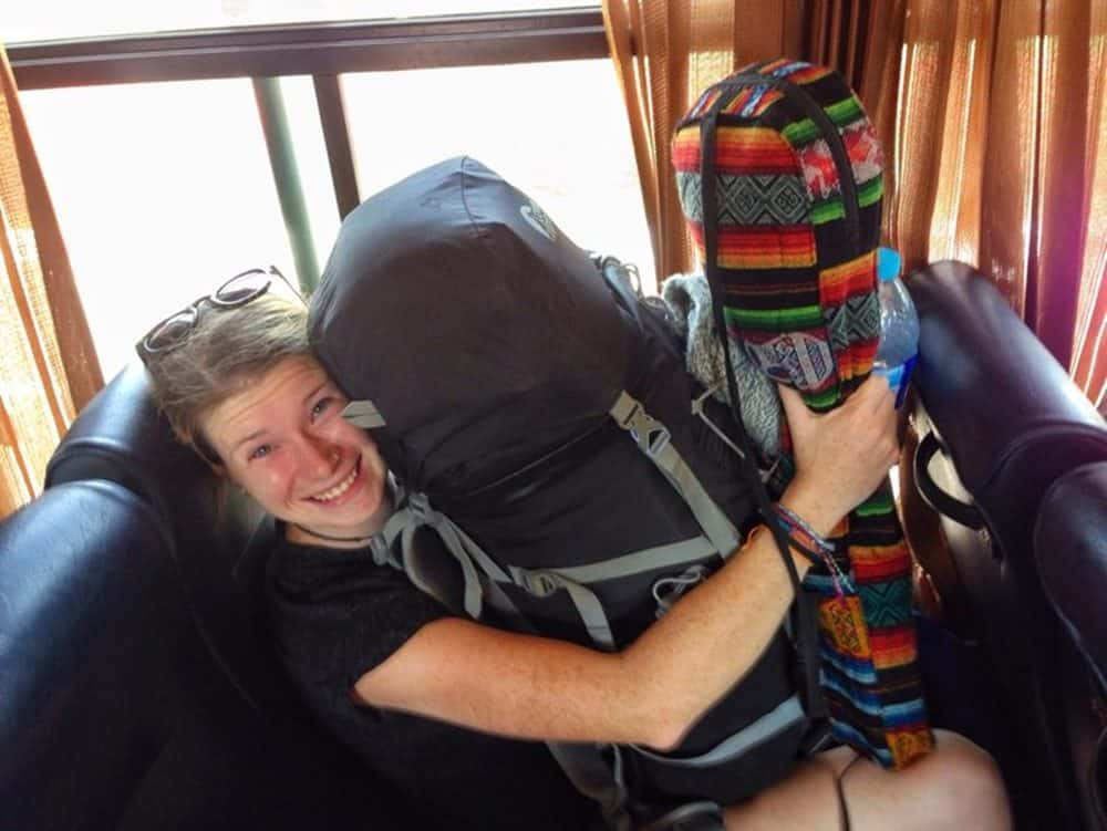 Sarah on bus carrying backpacks