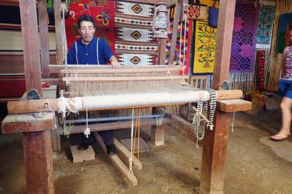 man-colorful-matts-by-hand-on-a-wooden-loom