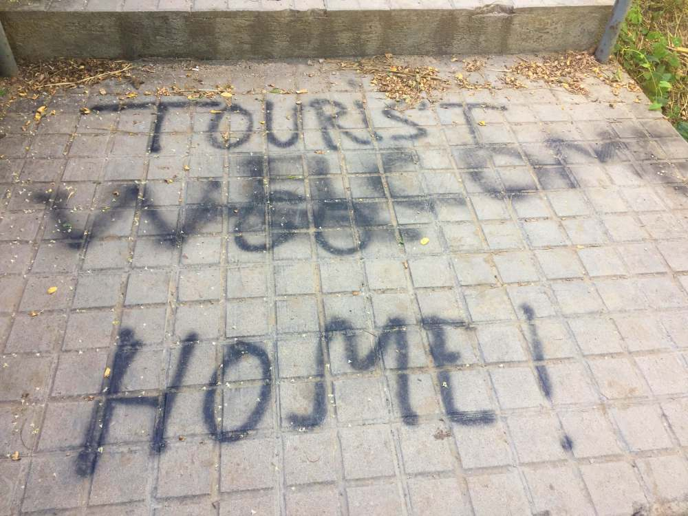 Anti tourist graffiti crossed out Parc del Guinardó