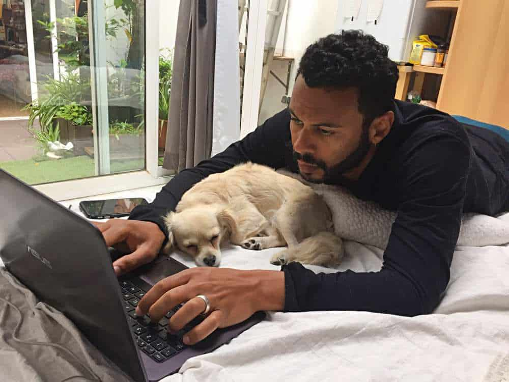 James working on his laptop on the bed with a dog