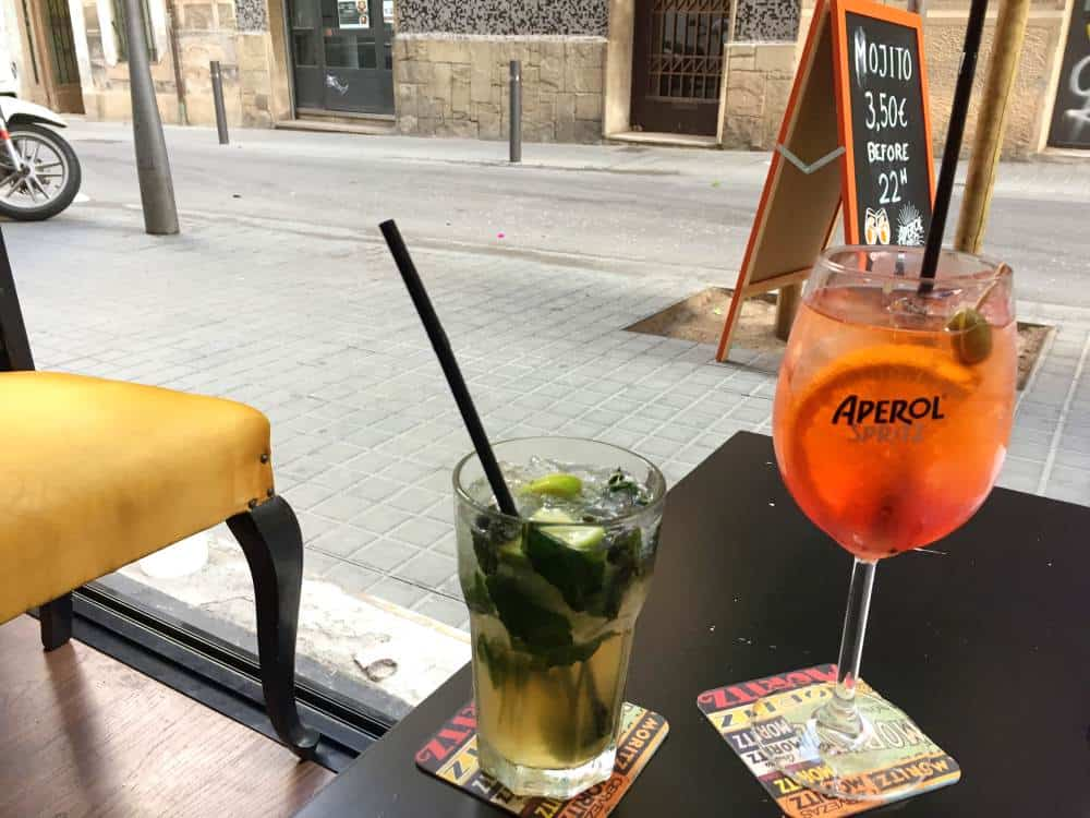 Mojito and aperol spritz cocktails on table