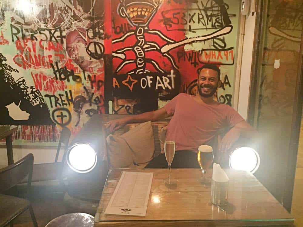 James sat on seat with drinks inside The Hideout Bar in Gracia