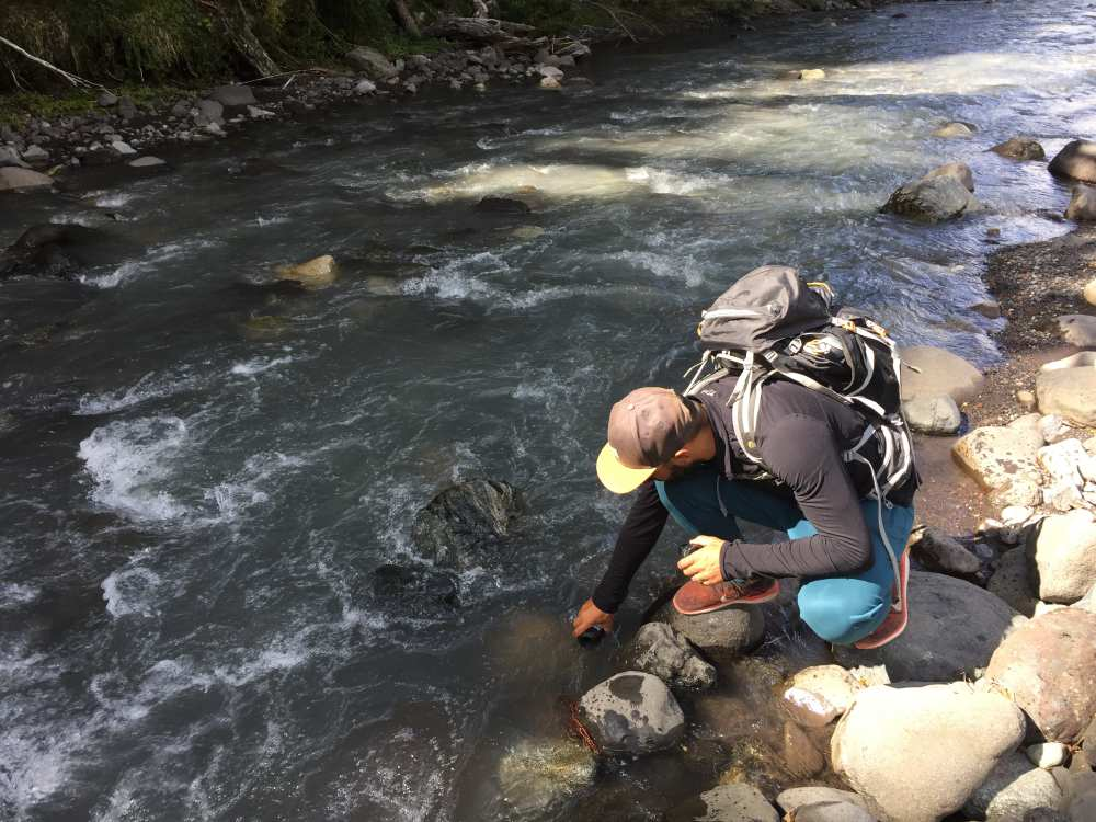 filling water bottle with glacier water from river castano overo
