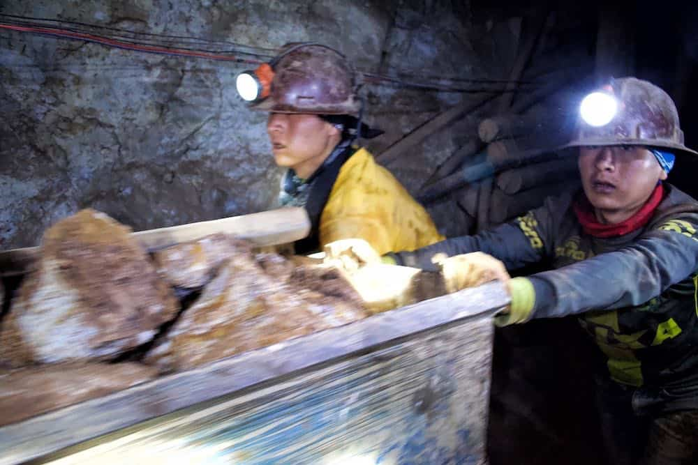 miners pushing cart inside Cerro Rico mine